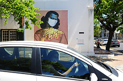 South Africa - Cape Town - 12 October 2020 - A women wearing a protective mask drives past Vladimir Tretchikoff's 'Chinese Girl', located on the corner of Plein and Drostdy streets in Stellenbosch. Masked Masterpieces, a compelling outdoors arts initiative sponsored by private individuals and companies, has taken the shape of a supersized and striking visual reflection on the challenges of our time. This is part of a public art initiative launched in Stellenbosch earlier this year and presents large scale reproductions of portraits by some of South Africa's most renowned artists. Dotted across numerous galleries and museums throughout Stellenbosch, the Masked Masterpieces are driven by Stellenbosch University bursary students in the 'missing middle' category, studying at the Faculty of Arts and Social Sciences. To support these students, who have been affected financially by COVID-19, they encourage residents and visitors to contribute to the bursary fund. The masked concept was inspired by Banksy (the British street artist famed for his wry urban art interventions), who is believed to have recently added a mask to his rendition of Vermeer's masterpiece Girl with a Pearl Earring. Picture: Henk Kruger/African News Agency(ANA)(ANATOPIX)
