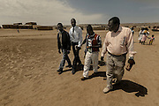 Tchikuteny coming from the church with three of his sons. In Angola?s Namibe desert, at Giraul, in the Namibe province, Tchikuteny, from the Mucubal tribe, is the leader of a big family, maybe the biggest family in the world.<br /> He is the chief leader, the manager and responsible for the entire village. <br /> In his village, Tchikuteny lives nowadays with most of his big family, his 33 wives, that were once 43, but 10 left the village, and most of their descendants.<br /> Tchikuteny maintains the registry of all the new-borns, totalizing 154 sons, and his grandsons, that are around 60. Nowadays, 4 new babies are on the way, and 3 great grand children were born recently.<br /> Huge harmony, love and respect transpire in the village atmosphere. The sense of a community is the pillar of their sustainability and sustenance and their autonomy depends prominently on cattle and agriculture that is made by the villagers. Nevertheless, Tchikuteny village is in close connection with their surrounding communities. Children attend Giraul School and there is proximity and relations with the extended family that lives in the surroundings.<br /> Being the spiritual leader of the community, Tchikuteny is also responsible for the weekly religious works that happens in the village church. <br /> This big family opened his doors to share with us their daily lives.