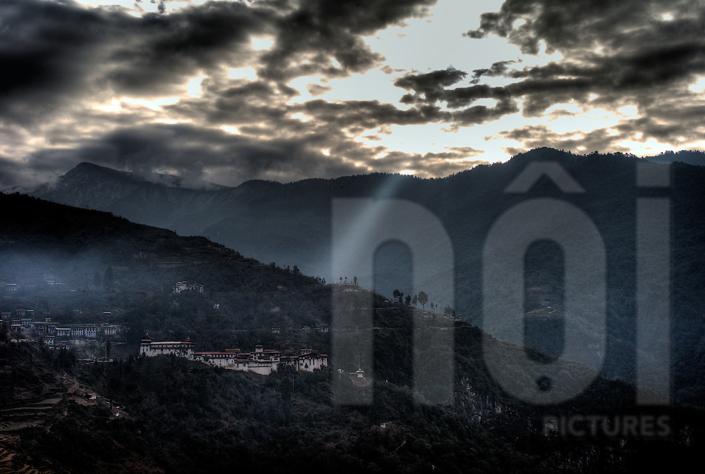 Mystical mountainous landscape with Trongsa Dzong fortress in foreground. Bhutan, Asia