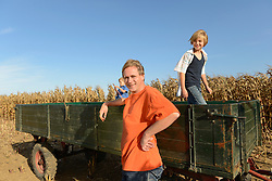 Father and sons standing by tractor, Bavaria, Germany