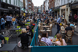 © Licensed to London News Pictures. 04/09/2021. LONDON, UK.  People socialising and dining al fresco on a Saturday evening in Old Compton Street in Soho.  The UK government has announced that there have been 37,578 Covid-19 cases in the last 24 hours, bringing the total in the last seven days to 245,354 with the total UK Covid-19 death total rising to 133,161.  Photo credit: Stephen Chung/LNP