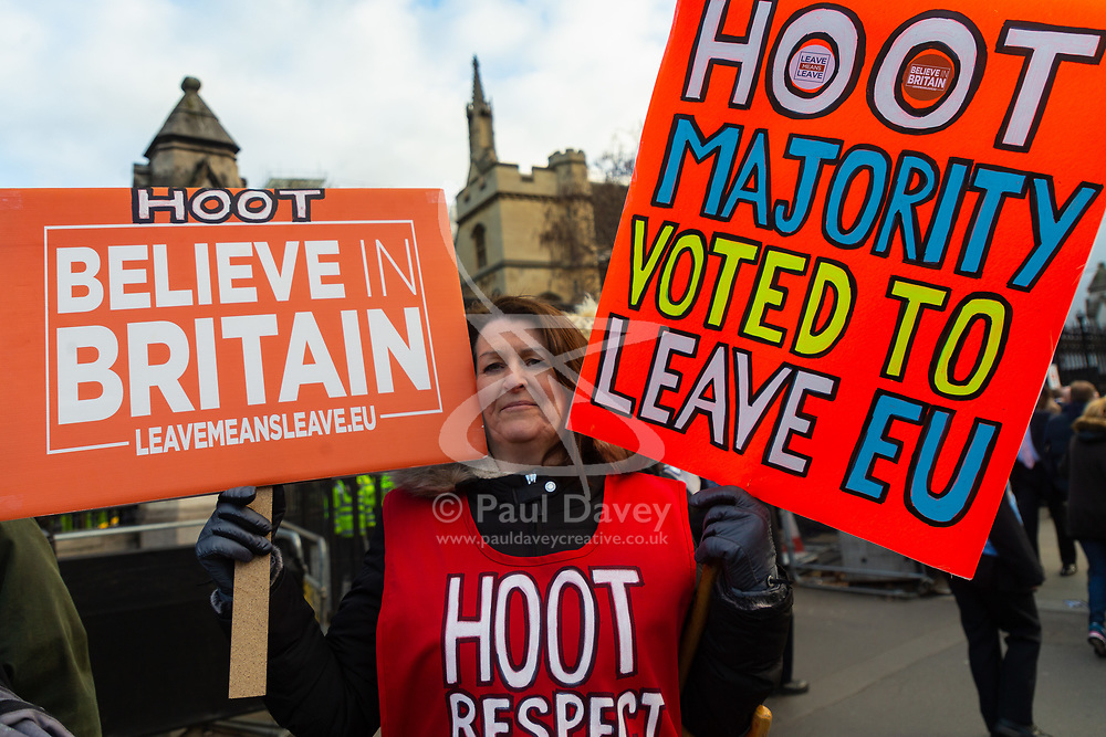 A woman's placards ask passing motorists outside the Houses of Parliament to hoot in support of Britain leaving the European Union. London, January 14 2019.