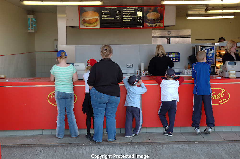 Family with overweight mother ordering fast food and drink at take away counter.
