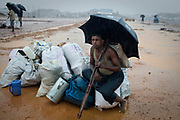A Rohingya refugee sits with his belongings as he waits to be relocated to safer ground due to the threat caused by intense rains in Balukhali, Camp 17, part of the refugee camp sheltering over 800,000 Rohingya refugees, Cox's Bazar, Bangladesh, June 12, 2018. Aid organisations are trying to move families to safer ground, but with hundreds of thousands of people on site, it is impossible to move them all.