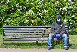 ©Licensed to London News Pictures 22/04/2020  <br /> Greenwich, UK. A man wearing a protective mask and gloves sitting on a park bench.  People out and about in Greenwich park, Greenwich, London exercising and enjoying the warm sunny weather. Photo credit:Grant Falvey/LNP