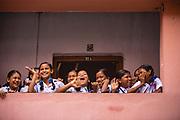 A group of schoolgirls laughing and waving to friends outside a classroom, Sursuna High School, Sursana, Kolkata, India