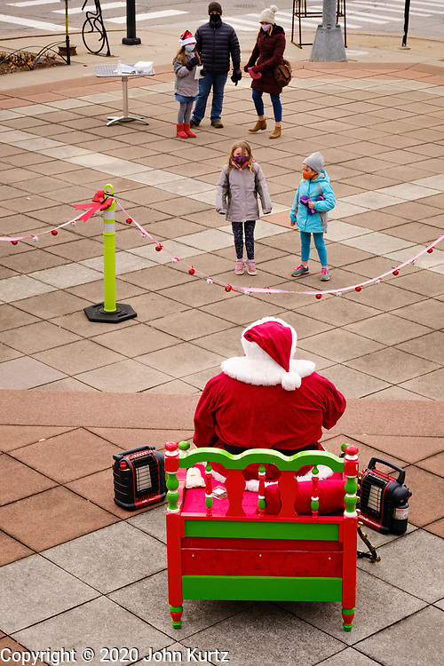 """29 NOVEMBER 2020 - DES MOINES, IOWA: A socially distanced Santa Claus talks to children from behind a rope line during the holiday """"Promenade"""" in the East Village neighborhood of Des Moines. This is the 19th year of the Promenade, a Des Moines tradition that draws shoppers and holiday revelers into the East Village neighborhood. This year's promenade is designed with CDC coronavirus guidelines in place, including social distancing and mask wearing.       PHOTO BY JACK KURTZ"""