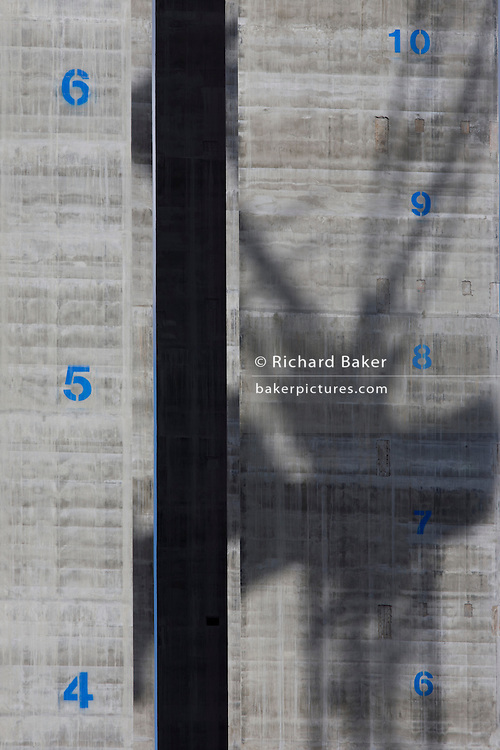 The shadow of a crane is spread across the concrete surface of a lift shaft with their floors marked vertically at 5 Broadgate, designed by Make Architects which will become the new home of UBS in London when fully occupied. Rising towards the sky is the tower-like structure with blue numbers of future storeys, stencilled on to the grey reinforced concrete. There will be 12 floors to this office complex of 700,000 sq feet (66,890 sq m), scheduled to be completed in 2016. The City of London is the capital's historic centre first occupied by the Romans then expanded during following centuries until today, it has a resident population of under 10,000 but a daily working population of 311,000.