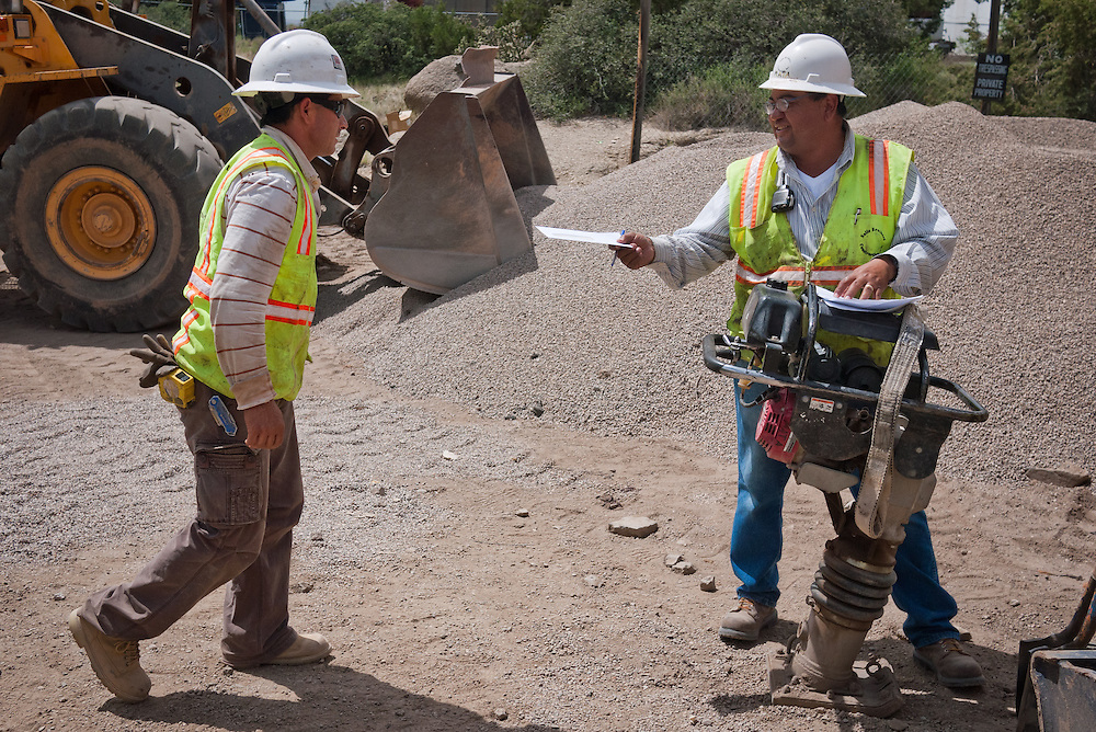 Juan Mata, right, passes out paychecks to employees after another week at work on the Carnuel Water Systems Improvement Project on Friday August 27, 2010. The $3.4 million project is supported by $2 million from the American Recovery and Reinvestment Act and will provide clean water to hundreds of Bernalillo County residents.