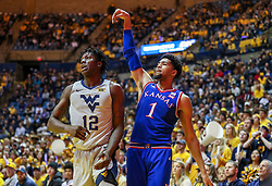 Jan 19, 2019; Morgantown, WV, USA; Kansas Jayhawks forward Dedric Lawson (1) shoots a three pointer in the corner over West Virginia Mountaineers forward Andrew Gordon (12) during the first half at WVU Coliseum. Mandatory Credit: Ben Queen-USA TODAY Sports