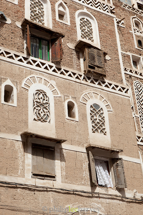 Facade of a typical building, made of mud, in the old city of Sana'a, a World Heritage Site which has been inhabited for over 2,500 years. Sana'a, Yemen.
