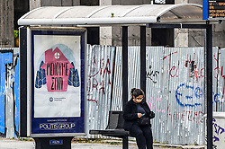 "A woman sits at a bas stop next with an adverting banner that reads ""Stay Home, Hellenic Republic-Health Ministry"" in Athens, Greece on March 23, 2020 as the country is battling hard to control the spread of the COVID-19, the novel coronavirus. Greek Prime Minister announced a ban on public movement starting at 06:00 am on March 23, 2020 to stem the spread of the global coronavirus pandemic in Greece.<br /> <br /> Pictured: <br /> Dimitris Lampropoulos  