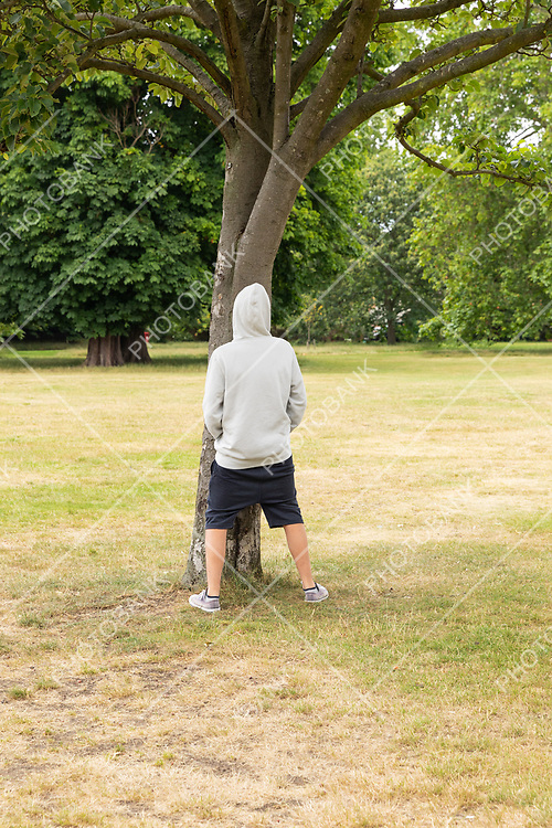 Young boy pisses on a tree in a park. Nobody else