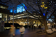 People walking along the riverside walkway at the National Theatre as dusk turns to evening on the Southbank, London, United Kingdom. The South Bank is a significant arts and entertainment district, and home to an endless list of activities for Londoners, visitors and tourists alike.