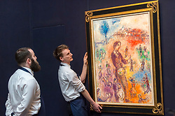 "© Licensed to London News Pictures. 20/02/2019. LONDON, UK. Technicians assess ""Le peintre à la fête"", 1982, by Marc Chagall (Est. £1.0-1.5m). Preview of Sotheby's Impressionist & Modern and Surrealist Art sales.  The auction will take place at Sotheby's New Bond Street on 26 February 2019.  Photo credit: Stephen Chung/LNP"