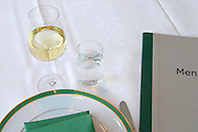 A restaurant table with a white linen table cloth set for one person, with plates, silver cutlery and green napkins, a glass of white wine and a glass of sparkling Swedish mineral water Ramlösa and the menu lying on the table waiting for the diner to start Ulriksdal Ulriksdals Wärdshus Värdshus Wardshus Vardshus Restaurant, Stockholm, Sweden, Sverige, Europe