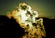 """The sun sets as """"Old Faithful"""" blows off steam in Yellowstone N.P., WY."""