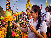 15 NOVEMBER 2018 - BANGKOK, THAILAND:  A woman prays and makes merit during the red cloth ceremony at Wat Saket, also called the Golden Mount. Wat Saket is on a man-made hill in the historic section of Bangkok. The temple has golden spire that is 260 feet high, which was the highest point in Bangkok for more than 100 years. The temple construction began in the 1800s during the reign of King Rama III and was completed in the reign of King Rama IV. A  red cloth (reminiscent of a monk's robe) is placed around the chedi at the top of  Golden Mount during the weeks leading up to the Thai holy day of Loy Krathong, which is November 22 this year.     PHOTO BY JACK KURTZ