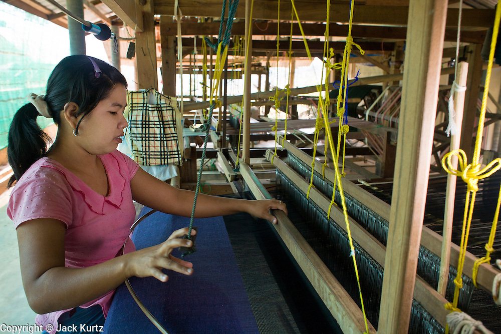 """19 FEBRUARY 2008 -- SANGKLABURI, KANCHANABURI, THAILAND: SABAE, a Burmese refugee from the Mon hill tribe, works in the weaving shop at Baan Unrak Children's Home in Sangklaburi, Thailand. Baan Unrak children's home and school, established in 1991 in Sangklaburi, Thailand, gives destitute children and mothers a home and career training for a better future. Baan Unrak, the """"Home of Joy,"""" provides basic needs to well over 100 children, and  abandoned mothers. The home is funded by donations and the proceeds from the weaving and sewing shops at the home. The home is a few kilometers from the Burmese border. All of the women and children at the home are refugees from political violence and extreme poverty in Burma, most are Karen hill tribe people, the others are Mon hill tribe people. The home was started in 1991 when Didi Devamala went to Sangklaburi to start an agricultural project. An abandoned wife asked Devmala to help her take care of her child. Devmala took the child in and soon other Burmese women approached her looking for help.    Photo by Jack Kurtz"""