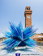 """The spiky blue """"Comet Glass Star"""" was made for Christmas 2007 by Master glass maker Simone Cenedese in Murano and displayed at Campo Santo Stefano, under the 1890 clock tower. Murano is a series of islands linked by bridges in the Venetian Lagoon, in northern Italy, Europe. To reduce the threat of fire to Venice, all glassmakers were forced to the island of Murano in 1291 AD. Venetian glass is world-renowned as colorful, elaborate, and skillfully made. Once an independent comune, Murano is now a frazione of the comune of Venice. The Republic of Venice was a major maritime power during the Middle Ages and Renaissance, a staging area for the Crusades, and a major center of art and commerce (silk, grain and spice trade) from the 1200s to 1600s. The wealthy legacy of Venice stands today in a rich architecture combining Gothic, Byzantine, and Arab styles. This panorama was stitched from 4 overlapping photos."""
