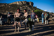 Dos indígenas rarámuris llamados pascolas danzan alrededor de una pequeña cruz forrada con hojas de pino acompañados de un par de músicos con violín y tambor durante la Semana Santa en Norogachi, México, el 11 de abril de 2009.