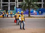 """12 FEBRUARY 2019 - SIHANOUKVILLE, CAMBODIA: Chinese construction workers walk back to a labor camp near the Blue Bay, a Chinese financed resort and casino development, in Sihanoukville. There are about 50 Chinese casinos and resort hotels either open or under construction in Sihanoukville. The casinos are changing the city, once a sleepy port on Southeast Asia's """"backpacker trail"""" into a booming city. The change is coming with a cost though. Many Cambodian residents of Sihanoukville  have lost their homes to make way for the casinos and the jobs are going to Chinese workers, brought in to build casinos and work in the casinos.      PHOTO BY JACK KURTZ"""