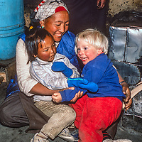Lakpa Doma Sherpani and her daughter play with 3-year old Ben Wiltsie by the hearth in their hom in Namche Bazaar, leading town of the Sherpas in Nepal.