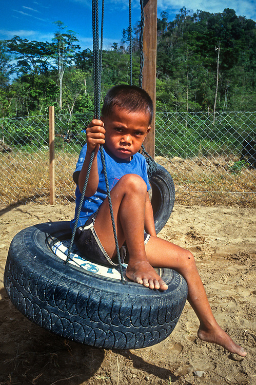 Young boy on make shift tyre swing Borneo, Malaysia, SE Asia