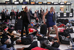 RETRANSMITTED CLARIFYING CAPTION<br /> Campaigners portray normal passengers as others stage a mass 'Die-In' in Terminal 2 at Heathrow Airport, to protest against aviation expansion ahead of the government's decision on increasing London's airport capacity.