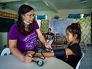 20 JANUARY 2018 - CAMALIG, ALBAY, PHILIPPINES: LAUGI NUAL, a midwife with a rural health unit takes a girl's blood pressure in the clinic at the Barangay Salugan evacuee shelter in a school in Camalig. There are about 870 people living at the shelter. They won't be allowed to move back to their homes until officials determine that Mayon volcano is safe and not likely to erupt. More than 30,000 people have been evacuated from communities on the near the Mayon volcano in Albay province in the Philippines. Most of the evacuees are staying at school in communities outside of the evacuation zone.   PHOTO BY JACK KURTZ