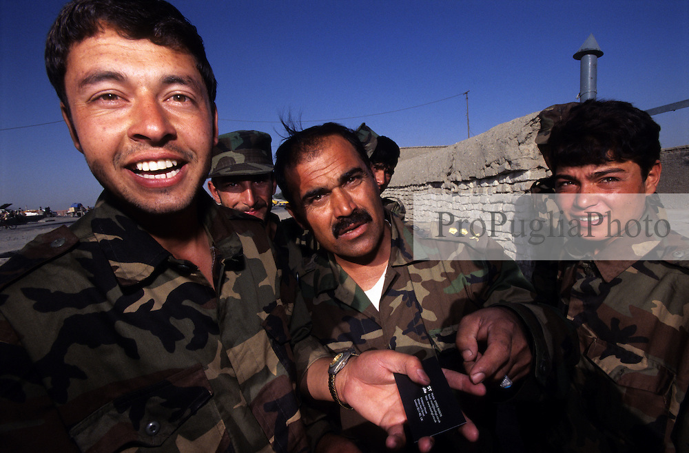 Afghan soldiers at their barracks in Kabul. Due to a very low army salary, Aziz, the soldier holding a business card, sells clothes at the Friday's market.