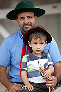 Father and son sitting on a horse portrait at a Gaucho cowboy Rodeo, Flores de Cunha, Rio Grande do Sul.