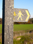 Close up of footpath sign with yellow human figure walking and direction arrow pointing the way, Wiltshire, England, UK