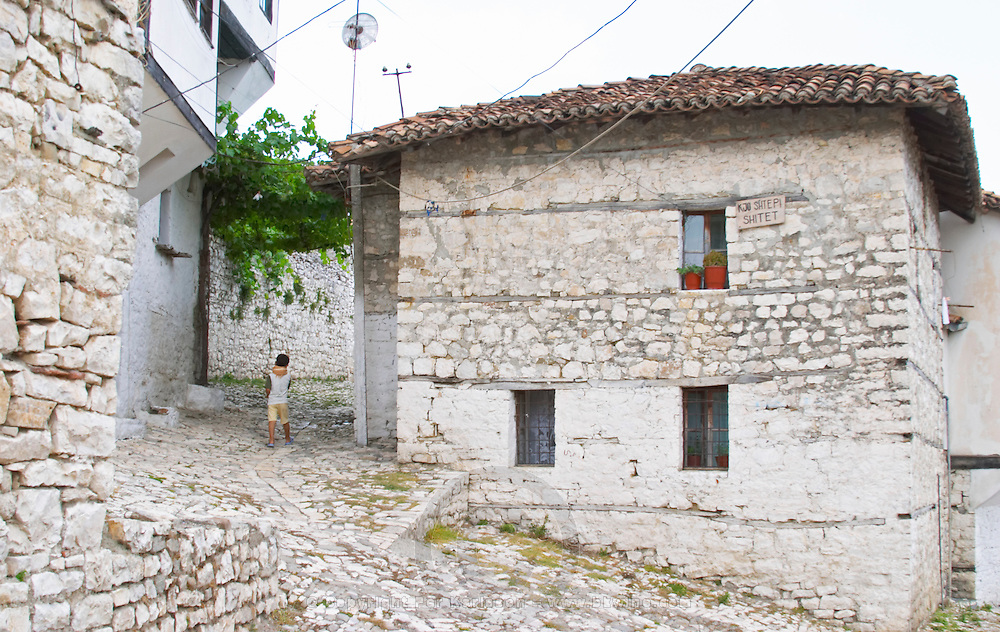 Traditional ottoman white stone houses, a young boy child walking on the cobble stone street. A sign on the house saying that the house is for sale. Berat upper citadel old walled city. Albania, Balkan, Europe.