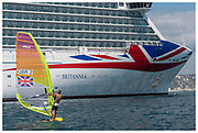 Olympian, Tom Squires windsurfing past the MV Britannia P&O cruise ship at Weymouth Bay in Portland, Dorset in the United Kingdom. At the time, seven large cruise ships were docked at Weymouth Bay due to the Covid-19 pandemic. July 2020.