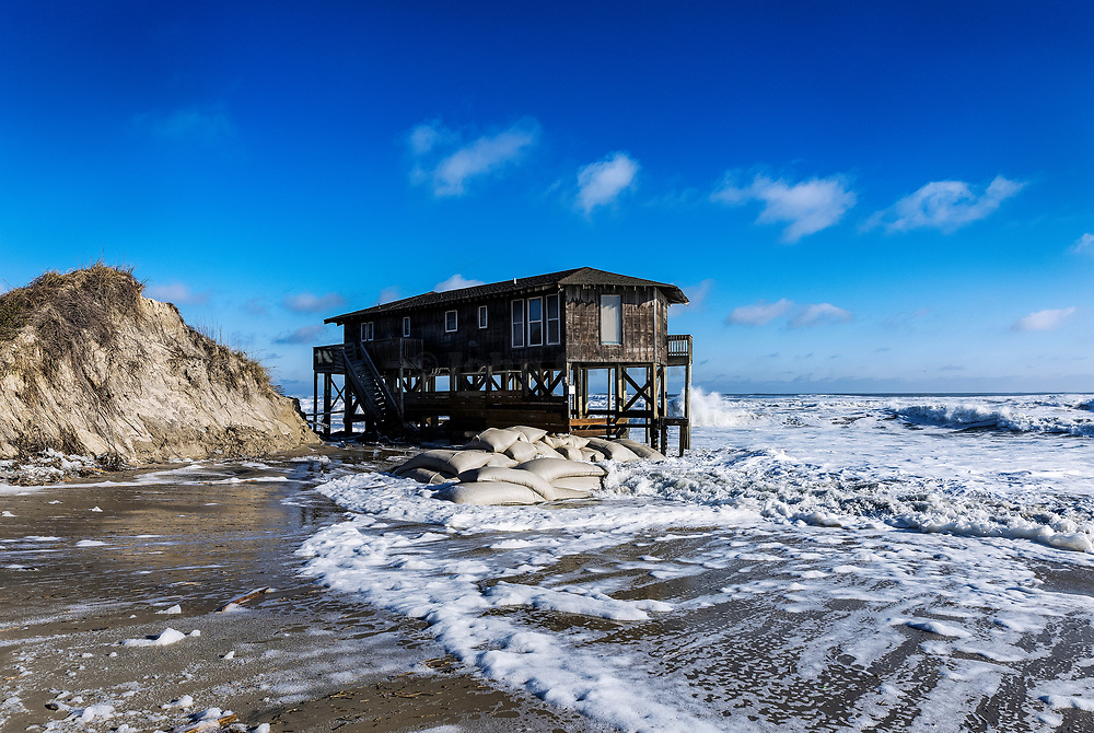 Beach house on stilts surrounded by high tide surf, Nags Head, Outer Banks, North Carolina, USA