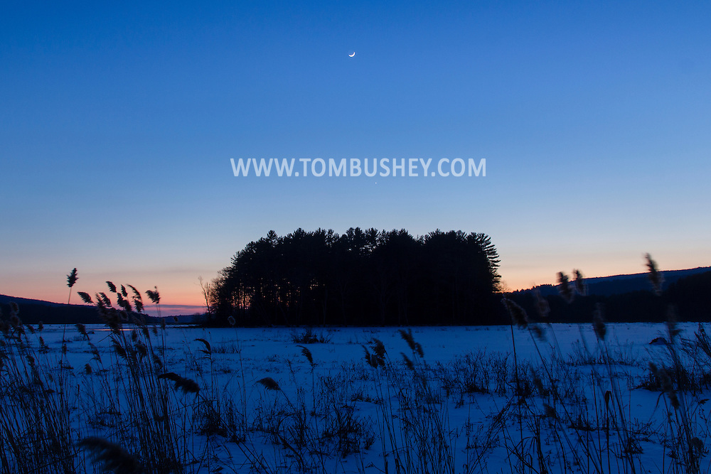 Mamakating, New York - The crescent moon shines in the sky over the Bashakill Wildlife Management Area after sunset on Jan. 22, 2015. The planet Venus is visible below the moon and above the trees.