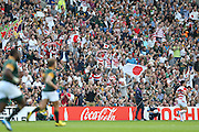 Japanese fans celebrate a try during the Rugby World Cup Pool B match between South Africa and Japan at the Community Stadium, Brighton and Hove, England on 19 September 2015. Photo by Phil Duncan.