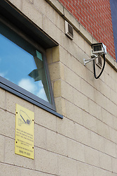 CCTV camera mounted on a building with sign