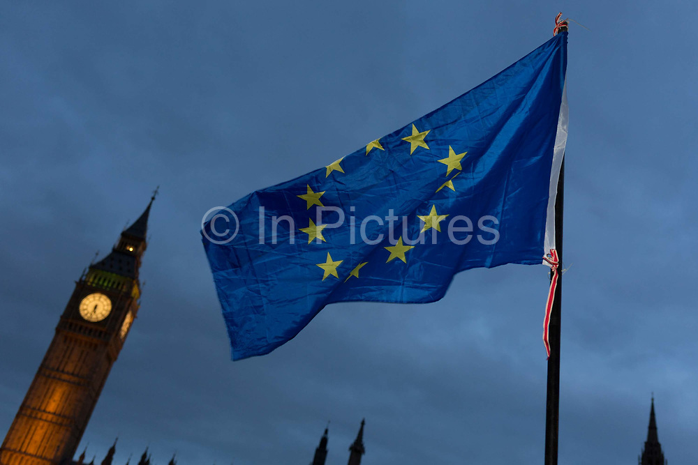 An EU flag is waved in front of the British parliament as the British government debated US President Donald Trumps state visit to the UK, thousands of protesters gathered in large numbers against the trip which would potentially cost millions of Pounds in security alone, on 20th February 2017, in Parliament Square, London, UK. The visit comes after two online petitions received more than the 100,000 signatures required for such a debate to be considered in Parliament. A petition against the state visit got 1.85m signatures, while one supporting it got 311,000. Campaigners protested against the hatred, racism and division that Donald Trump is trying to create. Prime Minister Theresa May announced the state visit during her visit to Washington in January.