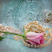 Pearls, pink rose and crystal with vintage background.