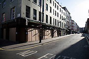 Bars and restaurant boarded up and closed down on Old Compton Street in Soho, at the heart of the West End under Coronavirus on 23rd March 2020 in London, England, United Kingdom. Following government advice most people are staying at home leaving the streets quiet, empty and eerie. Coronavirus or Covid-19 is a new respiratory illness that has not previously been seen in humans. While much or Europe has been placed into lockdown, the UK government has announced more stringent rules as part of their long term strategy, and in particular social distancing.
