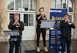 "© Licensed to London News Pictures. 27/07/2015. Bristol, UK.  ""Fanfare for Bristol"", titled ""At the Top of the Tide"", composed by David Mitcham, commissioned by Bristol Proms 2015.  Picture shows trumpeters l-r: Chris Hart, Helen Whitemore, Gideon Brooks, performing live for the Mayor of Bristol, George Ferguson and Artistic Director of the Bristol Old Vic, Tom Morris for the first time at Bristol's famous Temple Mead train station, heralding the opening of the Bristol Proms 2015.  David Mitcham's  ""At the Top of the Tide"" was inspired by 'Bristol's inextricable links to the sea'.  The first performance by Arc Brass took place outside the Engine Shed, and throughout the day, performances took place at the Watershed, Pero's Bridge, the Wills Memorial Bell Tower and finally at Bristol Old Vic itself. David Mitcham, who has worked extensively for the BBC Natural History Unit based in Bristol said: ""I am thrilled that my Fanfare ""At the Top of the Tide"" has been chosen for the city of Bristol and to open Bristol Proms 2015. I hope the Fanfare represents the rich diversity of Bristol, its maritime and industrial heritage as well as being a celebration of the spirit of the city and the energy it will carry into the future.""  Bristol Proms 2015 runs from today, 27th July to 1st August and features some of the world's finest musicians including Alison Balsom, Miloš Karadaglić, Pumeza Matshikiza and Daniel Hope.  Photo credit : Simon Chapman/LNP"