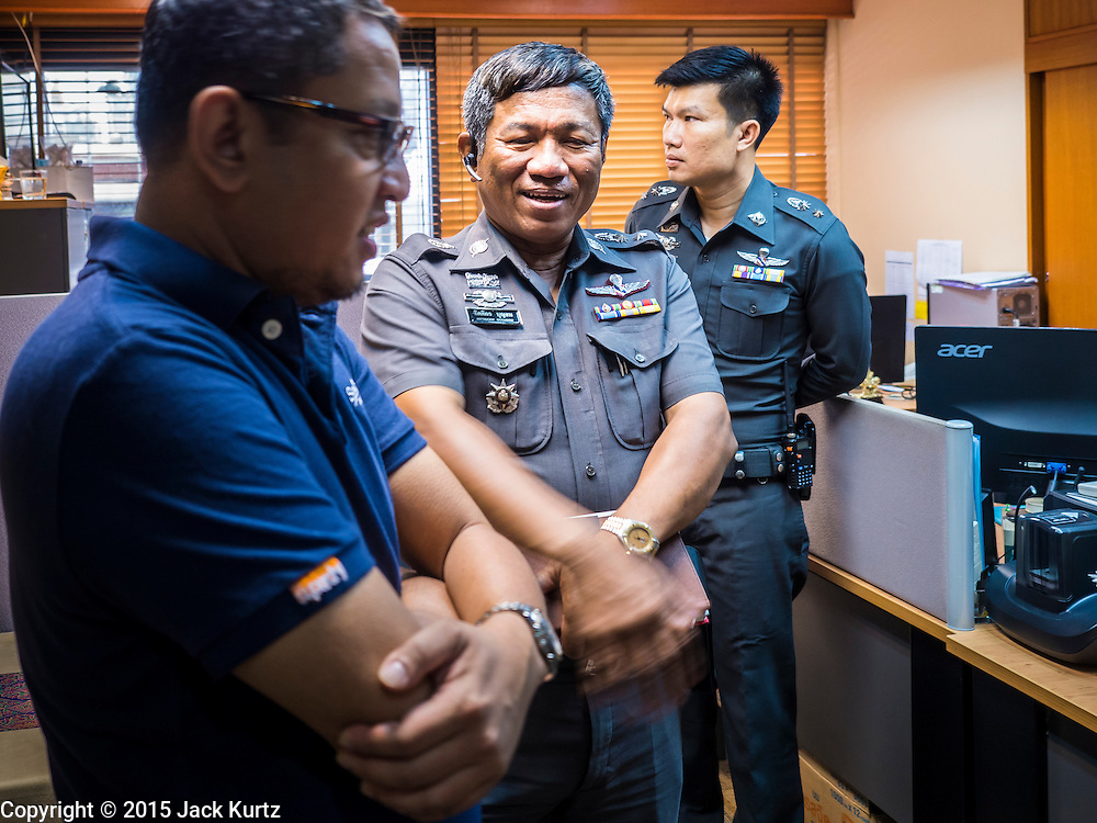 """26 JUNE 2015 - BANGKOK, THAILAND:  Thai Police Colonel KITTIGORN BOONSOM, center, tells representatives of the Foreign Correspondents' Club of Thailand (FCCT) that a scheduled announcement by Human Rights Watch (HRW) about human rights in Vietnam was cancelled by order of the Thai government. HRW was scheduled to launch a new report, """"Persecuting 'Evil Way' Religion: Abuses against Montagnards in Vietnam"""", at the FCCT in Bangkok Friday morning. The report made no mention of the human rights situation in Thailand. The Thai Ministry of Foreign Affairs (MFA) contacted HRW Thursday afternoon and asked them to cancel the program because it was a """"sensitive"""" matter that could impact on Thai-Vietnam relations. HRW told the MFA that they would go ahead with the report's release. Friday morning, before the report was scheduled to be released, Thai police officers arrived at the FCCT and cancelled the event. Phil Robertson, deputy director of Human Rights Watch's Asia division, said, """"By stepping in to defend a neighboring state's human rights violations against a group of its people and interrupting a scheduled press conference, Thailand's military junta is violating freedom of assembly and demonstrating its contempt for freedom of the press.""""      PHOTO BY JACK KURTZ"""
