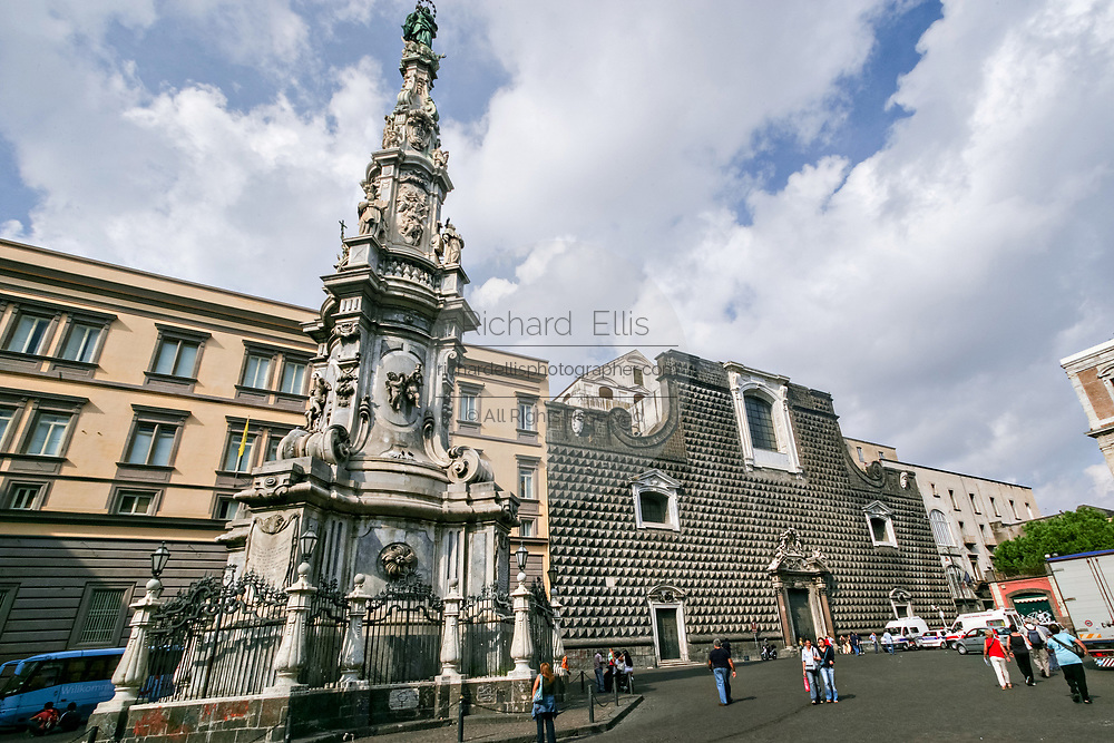 The Spire or Guglia of the Immaculate Virgin and Church of Gesu Nuovoin in Naples, southern Italy. The Church of Gesu Nuovo was originally a palace built in 1470 for Roberto Sanseverino, Prince of Salerno. The unusual building is faced with with rustic ashlar diamond projections.