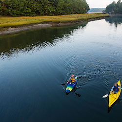 Two kayakers enjoy an early morning paddle on the York River in York, Maine.