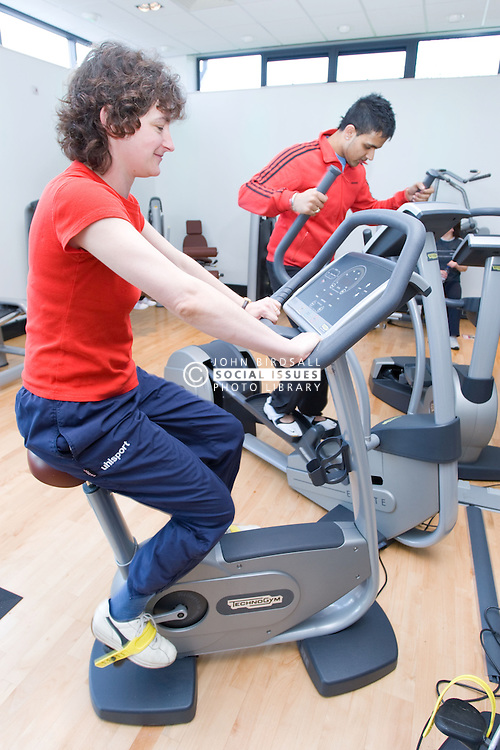 People using exercise bikes at their sports leisure centre,