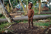 A small naked child cries when he sees a white foreigner in the Village of Komor in the Asmat Swamp. Irian Jaya, Indonesia. Irian Jaya was renamed Papua (province).
