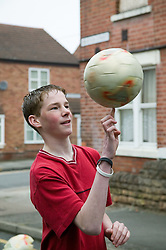 Boy spinning a football on his fingertips,