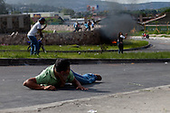 5 July 2009 - Tegucigalpa, Honduras - A supporters of ousted Honduras' President Manuel Zelaya takes cover from a barrage of gun fire by soilders at the Tegucigalpa airport.  President Zelaya was unable to land today, but pledged to return in the coming days. His supporters have been marching in the capital's streets since he was ousted last Sunday, but the protests have increased dramatically in the last few days.